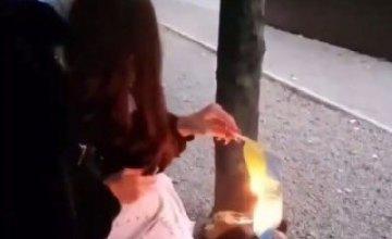Полиция установила личность девушки, которая подожгла Государственный флаг Украины